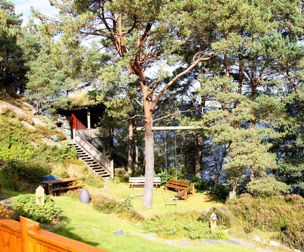 Tømmerhytten og hagen med bålplass